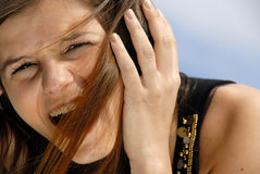Girl Listening. Girl or young woman listening to audio, hand holding earphone device to her ear, outdoors, hair blowing in face Stock Photography