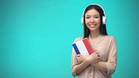 Girl listening French audio lessons in headset, book in hands, translations. Stock footage stock video footage