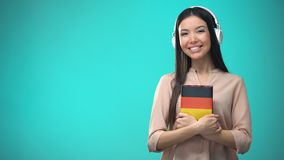 Girl listening German audio lessons in headset, book in hands, translations. Stock footage stock video footage