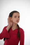 Girl listening with hand to ear. Isolated on a white background stock image