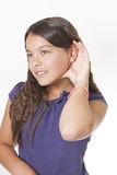 Girl listening with hand to ear Royalty Free Stock Photography