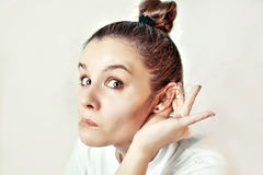 Girl listening with her hand on an ear Stock Photo