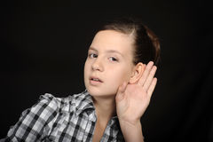 Girl listening with her hand on an ear Stock Images
