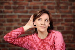 Girl listening with her hand on an ear Royalty Free Stock Photos