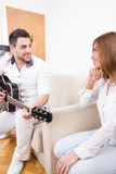 Girl listening a man while he is playing guitar Stock Photography