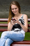 Girl is listening mp3. Cute attractive girl is listening music in earphones plugs on mp3 player or mobile phone Stock Image