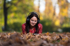 Girl Listening Music In The Autumn Sunshine Stock Images