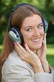Girl is listening music with headphones. On nature Stock Photography