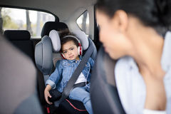 Girl listening music in headphones while driving in car. Little girl listening music in headphones while driving in car royalty free stock photo