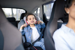 Girl listening music in headphones while driving in car. Little girl listening music in headphones while driving in car stock photography