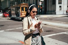 Girl listening music with headphones. Fashion college girl listening music with headphones and smart phone online walking on street in san francisco with cable royalty free stock photo