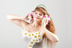 Girl listening music in headphones of flowers Stock Image