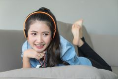 Girl listening music headphones lying on sofa at home.happy fac. Girl listening music headphones lying on sofa at home. Young Asian woman happy smiling face with stock images