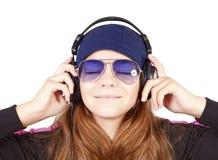Girl listening music by headphones over white Stock Images