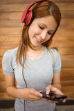 Girl listening music with headphones while sending message. In the city Stock Image