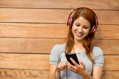 Girl listening music with headphones while sending message Royalty Free Stock Images