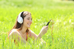 Girl listening music with headphones and smart phone in a field Royalty Free Stock Photos