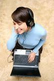 Girl listening music from laptop Stock Image