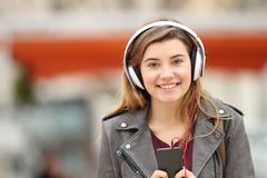 Girl listening music and looking at you. Front view of a happy young adult girl listening music on line with headphones and looking at you in the street Royalty Free Stock Image