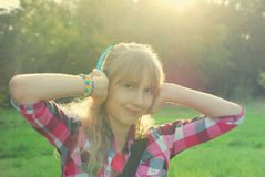 Girl listening music on the meadow in vintage style Stock Images
