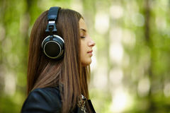 Girl listening music outdoor Stock Image