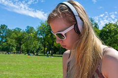 Girl listening music in park Royalty Free Stock Photo