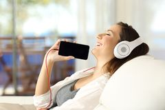 Girl listening music and showing phone screen indoors. Side view portrait of a happy girl listening music and showing blank phone screen sitting on a sofa in the Stock Photography