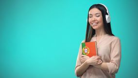 Girl listening Portuguese audio lessons in headset, book in hands, translations. Stock footage stock footage