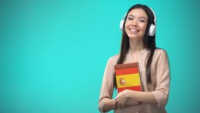 Girl listening Spanish audio lessons in headset, book in hands, translations. Stock footage stock footage
