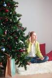 Girl listening to Christmas carols Stock Photography