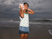Girl listening to the conch Royalty Free Stock Photography
