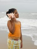 Girl listening to a conch Stock Image