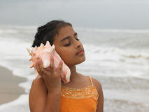 Girl listening to a conch. Cute girl listening to a conch Stock Image