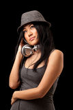 Girl listening to headphones. A young asian girl dressed in stylish clothes listening to music from dj style headphones Stock Photos