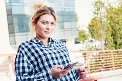 Girl listening to mp3 streaming service on the phone. Happy and cheerful young girl listening to music on the phone stock photography