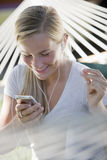 Girl listening to MP3 player and snapping fingers Stock Photos