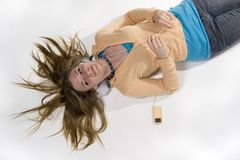 Girl listening to music. Pretty teen girl lying on floor listening to iPod Stock Images