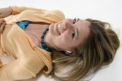 Girl listening to music. Teenage girl lying on floor listening to iPod Royalty Free Stock Photography