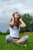 Girl listening to music. Girl sitting crosslegged on green grass looking up towards the sky with her eyes closed in enjoyment listening to music on headphones Royalty Free Stock Photo