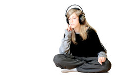Girl Listening To Music. A young girl listening to music while sitting on the floor Stock Photo
