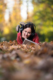 Girl Listening To Music On Autumn Leaves Stock Photography