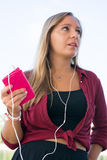 Girl listening to music. A beautiful young girl listening to music with earphones Royalty Free Stock Images