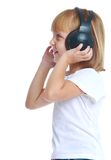 Girl listening to music with big black headphones Stock Photography
