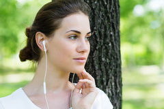 Girl listening to music coming from headphones. In park Stock Images