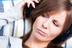 Girl listening to music with displeasure. Cute girl listening to music with some displeasure Stock Image