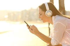 Girl listening to music downloading song using phone royalty free stock images