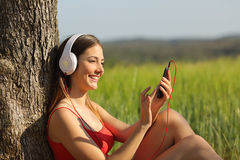 Girl listening to the music and downloading songs in a field. Girl listening to the music and downloading songs sitting in a green field wearing a red shirt royalty free stock image