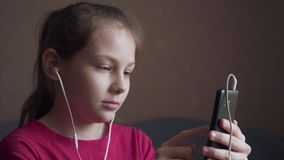 Girl listening to music from earings and feeling rhythm. Young girl listening to music from earings and feeling rhythm at home stock footage