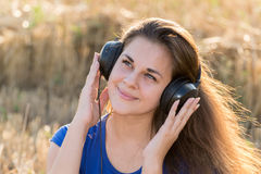 Girl listening to music in  field Stock Photo