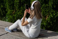 Girl listening to music on a headphone and looking in a smartphone. A woman sitting on the bench in the park on a sunny spring day royalty free stock image
